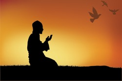 Silhouette of a Muslim praying during sunset.