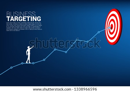 72eca25cc99 silhouette of businessman point to dartboard on line graph to center of  dartboard. Business Concept