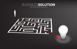 Silhouette of businessman with route path to exit the maze to light bulb. Business concept for problem solving and finding idea.