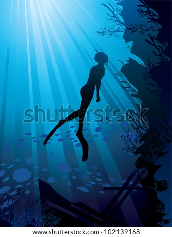 Silhouette of free-diver and marine reef on a sun ray in sea