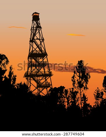 Silhouette of tall forest fire watch tower