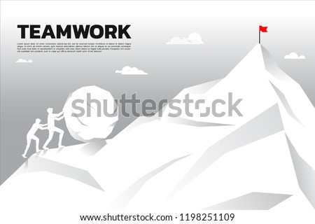 Silhouette of two businessman pushing the big rock to the top of mountain. concept of business challenge and teamwork.