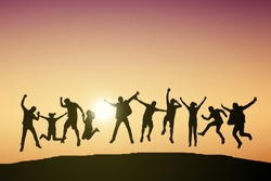 Silhouette of young man and woman jumping to celebrate success on top of hill, sky and sun light background.