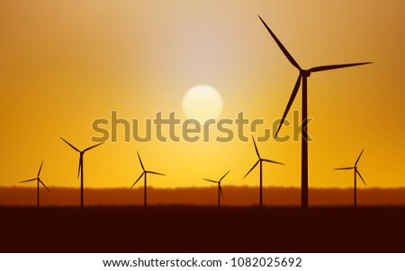 Silhouette wind turbines on land field with sunset sky background