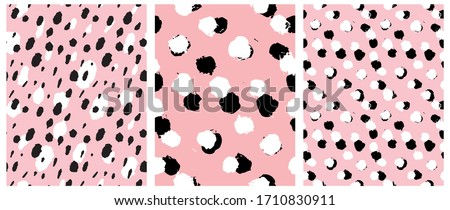 Simple Freehand Spots Seamless Vector Patterns. White and Black Hand Drawn Brush Dots Isolated on a  Light Pink Background. Rough Irregular Geometric Repeatable Print ideal for Fabric, Textile.