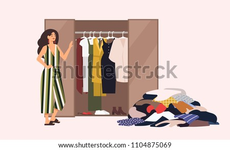 Smiling long-haired girl standing in front of opened closet with apparel hanging inside and pile of clothes on floor. Concept of minimalist capsule wardrobe. Cartoon vector illustration in flat style