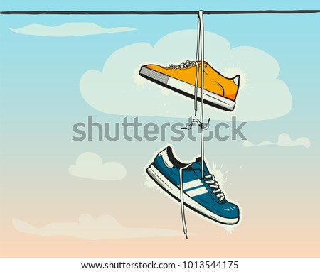 Sneakers hanging from a rope on the background of clouds