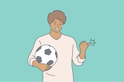 Sport, advertising, football, game concept. Young happy smiling african american man guy boy teenager character soccer player man standing with ball and pointing aside with finger. Active lifestyle.