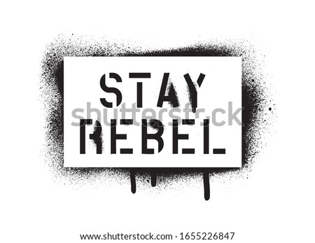 STAY REBEL quote. Spray paint graffiti stencil with copious leakage. A message for any personal or collective rebellion or dissatisfaction. Stock photo ©