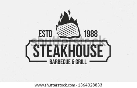 Steakhouse retro logo. Steak with fire flame. Barbecue restaurant logo, emblem, poster. Vintage design. BBQ Vector template logo.