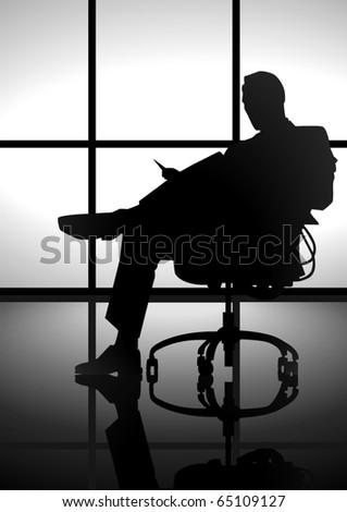Stock image of a man silhouette  sitting on a chair reading