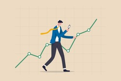 Stock market data analysis, financial research professional or investment and economic forecast concept, smart businessman analyst using magnifying glass look in details on market data rising graph.