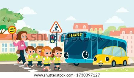 Teacher and school kids cross the street by crosswalk. Road traffic safety. Children, pupils babysitter, nurse, cross the street. Traffic lights.