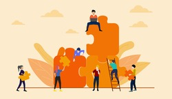 Teamwork concept. People working with giant jigsaw pieces on orange sky background