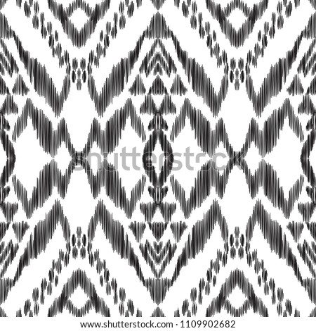 The abstract ikat pattern on ethnic style. Vector illustration in black and white color palette. Exquisite seamless texture can be perfect for background images, wallpapers, textiles, wrapping papers.