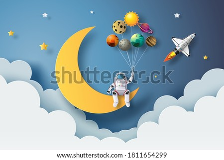 The astronaut is sitting on the moon holding planet balloons, paper cut style, flat-style vector illustration.