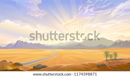 The desert view over the hill. Sunrise behind the mountains and a road across the desert.