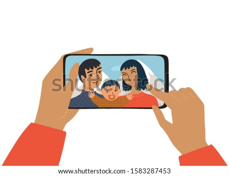 The female hand holds a smartphone. The concept of photography, chat, video call. The family smiles and takes a selfie. The mother and father and son take a photo on vacation.