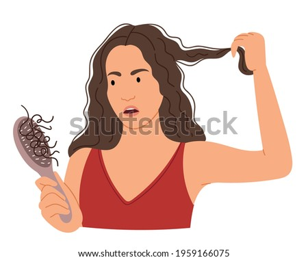 The girl is afraid that her hair is falling out.Hair loss after illness. Comb with hair. Scalp care at a trichologist.