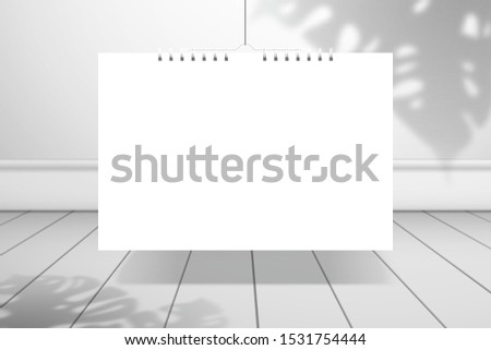 The shadow of a monstera plant falls on the wall behind a white blank spiral calendar or notebook that hangs over the plank floor. Realistic mockup for design