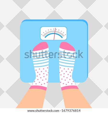 The young woman is weighed on scales. Female feet in socks are on an weighing-machine.