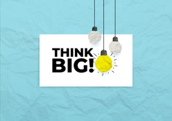 Think big. Slogan text. Yellow crumpled paper against the different white light bulb. Vector illustration. Isolated on blue background.