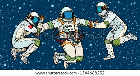 three astronauts in space in zero gravity. Pop art retro vector illustration kitsch vintage