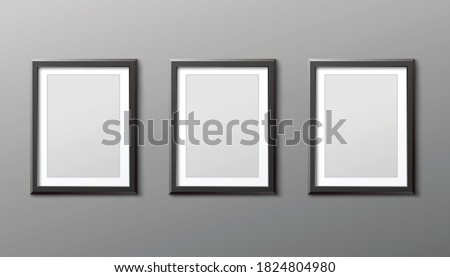 Three photo or picture frames hanging vertically on grey wall, realistic vector mockup illustration isolated on background. Template of blank black frameworks cadre. Photo stock ©