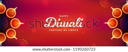 Top view of social media header or banner design decorated with illuminated oil lamps on glossy red background for Happy Diwali celebration.