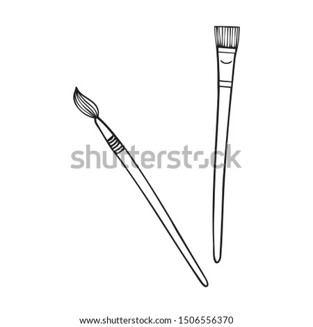 Two black and white paint brushes on a white backdrop #1506556370