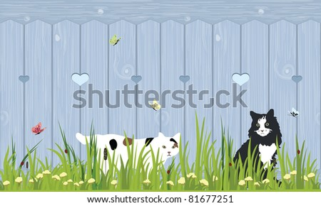 Two cats sitting in a grass field by a wooden fence