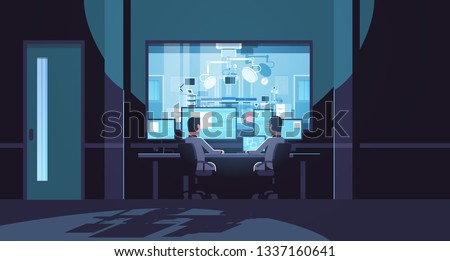 two men looking at monitors sitting behind glass window hospital operating table medical surgery room dark office interior surveillance security system flat horizontal