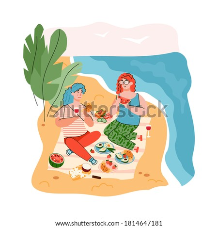 two women on beach picnic by