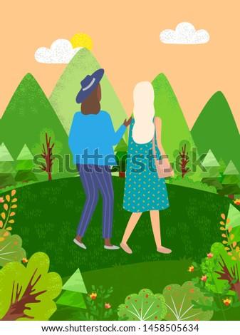 two women walking in green park