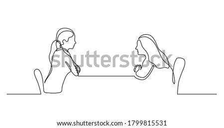 two young women sitting behind table talking Foto stock ©