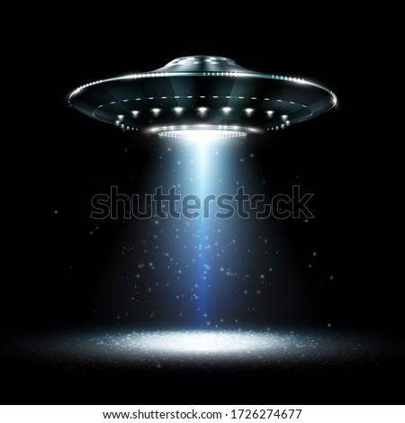 UFO. Unidentified flying object. Futuristic UFO on the black background. Photo-realistic vector illustration. Stock photo ©