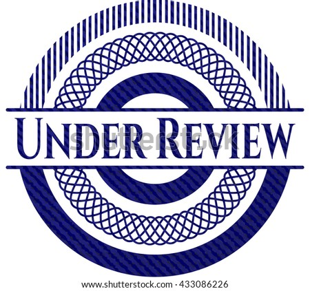 Under Review emblem with jean background