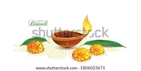 Vector illustration of Diwali festival Diya Lamp with rangoli at the bottom. Mango leaf and marigold flower kept on rangoli Stock photo ©