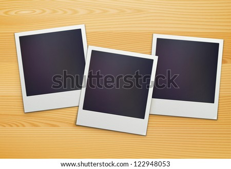 Vector illustration of three blank retro polaroid photo frames over wooden background
