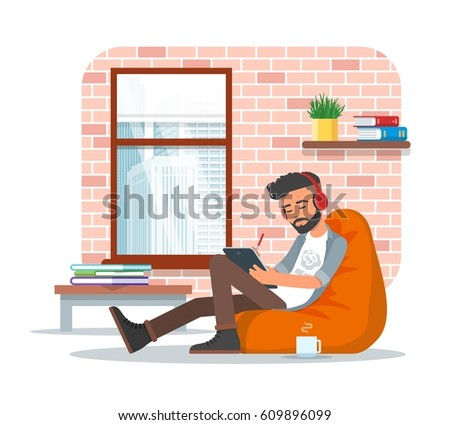 Vector illustration of young man sitting in bean bag chair and making use of tablet. Workplace interior, cartoon character, flat style design.