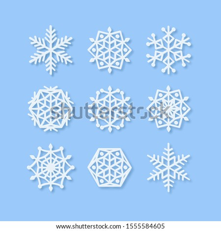 Vector Set of Paper Snowflake shapes. Symmetric Papercut snow flake silhouette isolated on blue. Winter season weather decoration icons. Christmas holiday, Noel greeting card. Origami art snowflakes