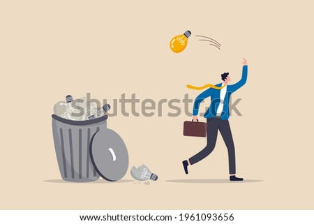 Wasted unworkable ideas, business failure or too many abandoned projects concept, frustrated businessman throw away lightbulb idea into full of junk idea in basket bin.
