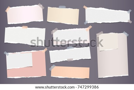 White and colorful ripped strips, notebook, note paper for text or message stuck with sticky tape on gray background.