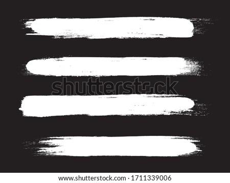 White brush stroke set isolated on black background. Trendy brush stroke vector for white ink paint, grunge backdrop, dirt banner, watercolor design and dirty texture. Brush stroke vector illustration
