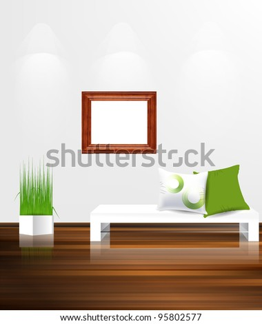 White couch with pillows against white wall with empty wooden frame.