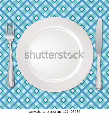 White plate with fork and knife on checkered tablecloth