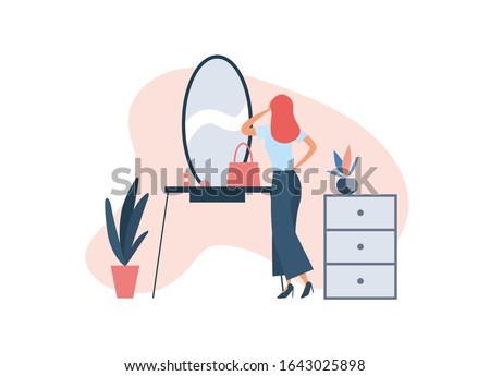 Woman applying makeup at home. Elegant lady standing near console mirror with cosmetic and bag and applying makeup while getting ready for work during beauty routine at home