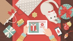 Woman purchasing Christmas gifts online using a tablet, her cat is playing with a bauble on the desk, holiday and celebrations banner