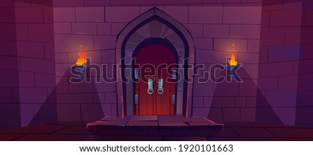 Wood door in medieval castle. Old gate in stone wall with flaming torches at night. Vector cartoon illustration of entrance to dungeon, prison or fortress. Wooden double doors with round knob knock