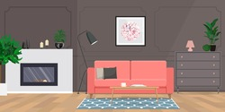 Wooden table on carpet in grey living room interior with fireplace and coral sofa.